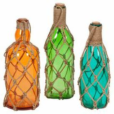 """Add an artful touch to your entryway console table or living room mantel with these eye-catching glass bottles, showcasing coastal-chic twine net accents.   Product: Small, medium and large bottleConstruction Material: Glass and twineColor: Orange, green and blueFeatures: Net accentsDimensions:  Small: 10.5"""" H x 3.3"""" Diameter  Medium: 10.5"""" H x 4"""" Diameter Large: 12"""" H x 3.5"""" Diameter"""