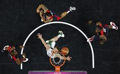 Lithuania's Martynas Pocius (C) looks at his shot past Lebron James (L), Deron Williams and Chris Paul (R) all of the U.S. during their men's preliminary round Group A basketball match at the Basketball Arena during the London 2012 Olympic Games August 4, 2012.   REUTERS/Mike Segar