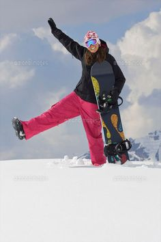 Female snowboarder playing around in the  (c)Ross Woodhall/cultura/Corbis