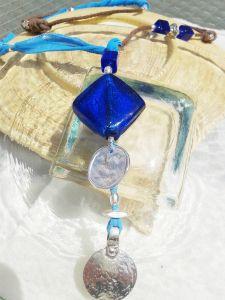 Collar asimétrico en cuero rústico color marrón  y seda pintada a mano, pieza central  cuadrado de cristal de murano azul,  cubos de vidrio monedas en zamak y peltre con baño plata. Ajustable.