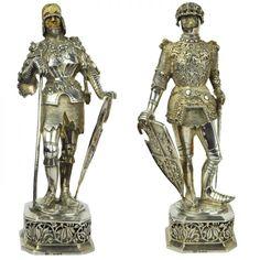 Par de figuras representando guerreiros medievais executadas em prata fundida, vazada, ricamente cinzelada e marfim. Contrastes europeus do séc. XIX. 21 cm e 22,5 cm.(uma falta capacete).