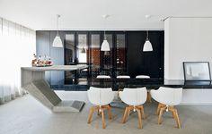 A mesa da sala de jantar é um prolongamento da bancada de mármore e possui apoio metálico central. Projeto do escritório Zemel   Chalabi