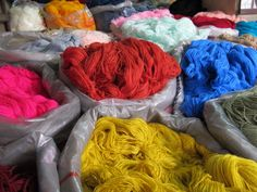 Sacks filled with brightly coloured sheep and llama wool