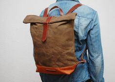 Waxed canvas backpack,brown color,use handles, base closures leather trimmings Golden antique gold color and the interior in cream cotton