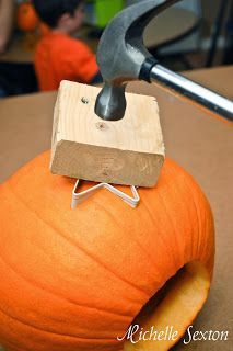 Carving a pumpkin using a cookie cutter. Now that's the way to do it lol