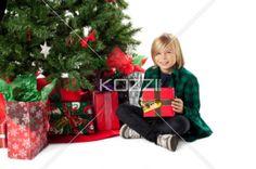 smiling boy with his christmas present, - Smiling boy with his christmas present sitting besides christmas tree, Model: Josh Chapman