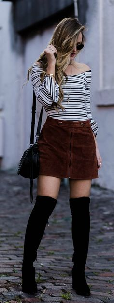 Boho winter outfit styled with striped bell sleeve bodysuit, suede mini skirt, black over the knee boots, and round Ray Ban sunglasses