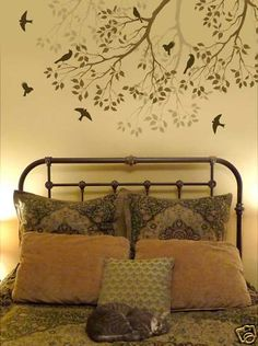 Iron wrought bed and tree Wall decal very subtle love the sleeping cat. What a low maintenance and lovely guest bedroom.