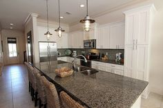 Contemporary Kitchen with Flat panel cabinets, L-shaped, Kitchen island, Simple granite counters, limestone tile floors