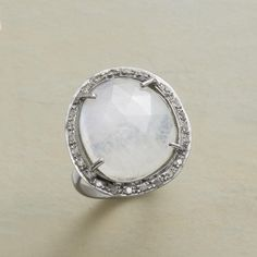 "MOON SWOON RING -- A pavé diamond and moonstone ring, in which diamonds set in antiqued sterling circle a faceted moonstone as it flirts with the light. Sterling silver band and pronged bezel. Whole sizes 5 to 9. 1-1/2"" dia."