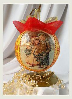 Bombka z przepięknym motywem dzieci w śnieżnej scenerii w kolorze żółtym i złotym. Ręcznie zdobiona, wielkość 9 cm, wykonana w technice Decoupage, ozdobiona wypukłymi, brokatowymi reliefami,...