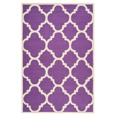 Anchor your living room seating group or master suite decor with this hand-tufted wool rug, showcasing a quatrefoil trellis motif in purple and ivory.