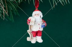 santa claus statue with a list and vase hanging on a christmas tree. - Santa Claus statue with a list and vase hanging on a Christmas tree against green background.