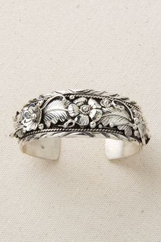 Sterling Silver Appliqué is a difficult and time consuming technique with a long history in Navajo design. Each sterling silver flower, feather, twist and leaf is handmade and individually soldered to the cuff bracelet. The sterling silver is lightly oxidized and polished to bring out the detail and texture. Appliqued pieces are in high demand …
