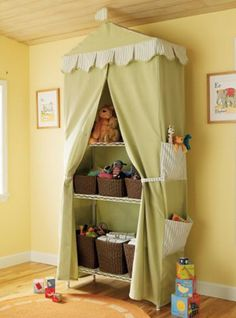 "Fabric ""tent"" conceals an inexpensive metal shelving unit.  Use matching wicker baskets to store toys.  Fabric baskets on the side hold smaller items."