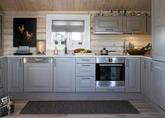 Norwegian Log Cabin is whitewashed on the inside, with grey cabinetry in the kitchen. The result is a bright and updated log-cabin design.