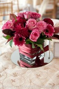 Pink and red rose centerpiece in a square glass vase