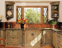 Custom Built French Country Kitchen Cabinets  These untique kitchen cabinets are constructed from antique doors, antique carved legs, antique carved columns, antique carved fragments and mouldings and recycled woods.  Features include corner niche cabinets, custom windows with leaded side opening windows, cast bronze hardware, custom granite countertops and  artisan hand-rubbed finishes. Kitchen Cabinets 7816D Lower, 8089E Upper 7777E Window Seacord Photo by Eric Swanson