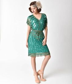Consider your prayers answered, darling. This gorgeous emerald green and glittering gold flapper dress exudes 1920s and 30s charm, hand crafted in intricately beaded mesh layered over an included matching slip. With impressive swaths of deco bursts and te