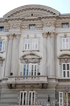 Photo made at a historic, elegant palace of Trieste in Friuli Venezia Giulia (Italy). The picture shows the high and central part of the facade, of very light color, formed by a balcony place within a capital supported by six columns, three for each side. On the balcony there are two twin doors by white frames like windows.