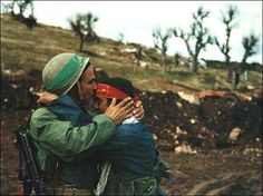 """A father kisses his son before the Iranian push """"over the top"""", 1985."""