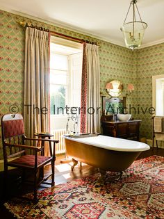 The bathroom walls are covered in a wallpaper by Robert Kime and the room is furnished with Arts & Crafts pieces