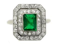 Antique emerald and diamond double cluster ring, circa 1905. A yellow gold and platinum ring set with one central rectangular step cut emerald in a platinum millegrain collet setting with an approximate weight of 1.50 carats, encircled by two octagonal pierced single rows of fifty four cushion shaped old cut diamonds with pierced divide and platinum millegrain bead settings with an approximate total weight of 1.62 carats, all above an ornate yellow gold geometric gallery, flanked by inward…