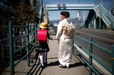 Fukushima, Japan: A girl walks with her mother after her first day at the Shimizu primary school via The Guardian 24 hrs in pics