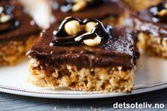 """Jeg bare DIGGER """"Snickerskake i langpanne""""! Utrolig god smak av salte peanøtter og kjeks og nydelig, søt og mørk sjokoladekrem. Med et så enkelt grep som å bytte mellom mørkog lys kokesjokoladen i glasuren, kan du variere denne kaken nokså betydelig. Her har jeg bruktkokesjokolade med 70 % kakaoinnhold, som gir en kake som blirtemmelig mørk i glasuren. Jeg synes da det er stilig å pynte kakestykkene med hele peanøtter og smeltet sjokolade. Med lys kokesjokolade får du en langt ..."""