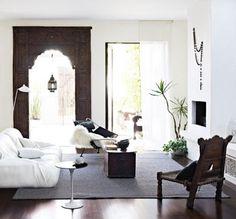 Moroccan Decor.  Dark wood, frame around door, open cut panels under window seats, color palette.