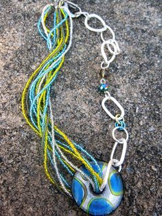 "'Water & Ash'  Twelve strands of turquoise, yellow and silver seed beads running through a 40mm glass round.  Aluminum chain links are light weight and will not tarnish and the large lobster clasp makes closure very easy. 18""L adjustable. $39  #jewelry  #women #fashion"
