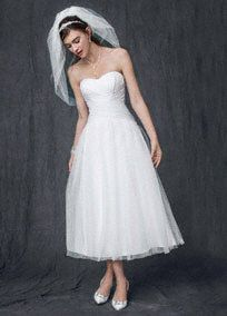 Give short and sweet a whole new meaning in this stylish strapless tea length wedding dress. Ruched bodice with inverted basque waist add texture and an appealing focal point. Full tulle skirt brings drama and a sophisticated twist. Sizes 0-14. White available in stores. Ivory by Special Order Back zip. Dry clean only. Imported.