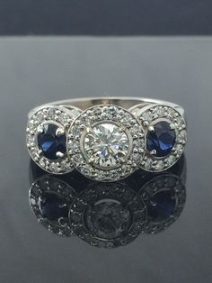 Diamond Halo Three Stone Engagement Ring With Blue Sapphire Accents in 14kw gold. by ThomasOJewelryDesign on Etsy https://www.etsy.com/listing/252500331/diamond-halo-three-stone-engagement-ring #DazzlingDiamondEngagementRings