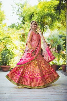 ombre lehenga , shaded pink lehenga , pink and gold gota work lehenga , sheer dupatta , sikh bride , raw silk lehenga , morning wedding , day wedding outfit , onion pink lehenga , bright pink lehenga , peachy pink bridal lehenga , twirling bride , spin