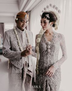 Saat akad, Ajeng mengenakan kebaya bludru hitam yang kental dengan suasana Jawa, sama seperti pakaian pernikahan orang tuanya dulu. Untuk resepsi, Ajeng mengenakan kebaya silver dengan Paes yang dipermanis dengan seragam sepupu-sepupunya yang menggunakan set beskap dan kebaya Kutubaru lengkap dengan aksesorisnya. Javanese Wedding, Indonesian Wedding, Kebaya Wedding, Wedding Gowns, Foto Wedding, Wedding Photos, Traditional Wedding, Traditional Outfits, Kebaya Jawa