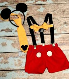 Boys 4pc Mickey Mouse Cakesmash set.  You will recieve the red Mickey shorts, black suspenders, Mickey Mouse ears and your choice between the yellow tie or bowtie.  Such a cute Boys Cake Smash Set.  Your little one will look so cute for his First Birthday Photo Shoot, which is fun to use for his Birthday Party Invitations as well.  Plus when he is opening up his gifts, blowing out the candles on his First Birthday Cake as well as diving into his Birthday Cake he will look adorable in his…
