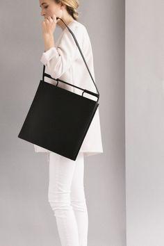 Opção para as moreninhas, bolsa minimalista de couro preto.