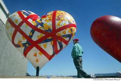 """Gary Bukovnik walks past his creation, """"Poppy Heart"""". As many as 130 5 foot tall heart instalations, designed by numerous artists and celebrities will fill San Francisco sidewalks, plazas and street corners during the spring and summer of 2004. event on 4/22/04 in San Francisco Michael Macor / San Francisco Chronicle Photo: Michael Macor / SF"""