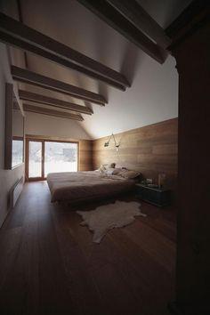 Wood floors wood walls bedroom in cabin in Slovenia with sheepskin rug