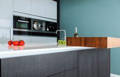 Een combinatie in de keuken van een kleurrijk, hoogglans wit en hout. Keukendealer: www.kwinteninterieur.nl