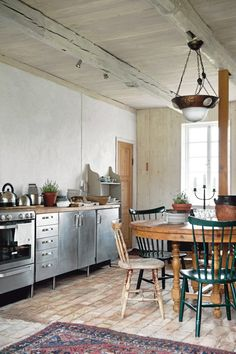 Chrome kitchen cabinets look fab alongside an eclectic mix of vintage furniture.