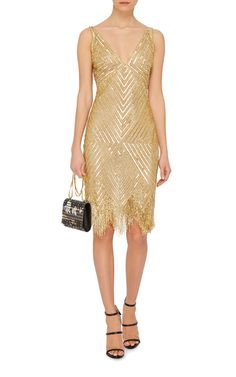 This sleeveless **Naeem Khan** cocktail dress features an allover sequined geometric design with a plunging V bodice and a mini length sheath silhouette with chevron fringe at the hem.