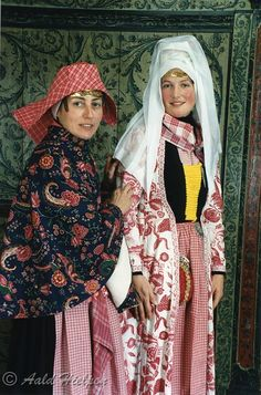 """On the left, an unmarried woman, wearing a kassakijntje (short coat), and over her shoulders a warm lined cape. On the right, the bride wears an antique 18th century costume. The design of this special wentke (long coat) is of white and red (called """"milk and blood""""), and was only worn at the wedding. She has just received the chatelaine (purse) for household money. The bodice lacing for this occasion is yellow. On her head she wears the bridal veil of thin batiste."""