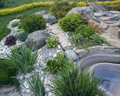 schöner Steingarten mit grünen Pflanzen une Wasserspiel
