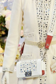 Chanel 2012 Pre-Autumn. WOW. White coat that looks like it has mirror embellishments, which would make sense given the ethnic Indian theme of this collection. I'm in love with this. Down the center, cuffs, pockets and on the hand bag flap and strap; beautiful gold belt with pearls, patterned gloves. Amazing.
