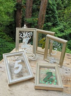 Framed Glass for Table Numbers Platinum...then use chalk markers to write numbers.  OR, use diamond mesh, moss, or ribbon to create textured numbers (that stick on with double sided adhesive).