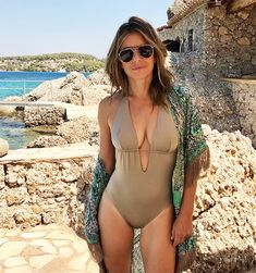 a0931a04856e2 Elizabeth Hurley soaks up the sun in a taupe one-piece swimsuit. Elizabeth  Carson