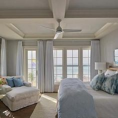 A white ceiling fan is fixed to a blue coffered ceiling in front of a bed placed on a white rug and accented with white and blue bedding and blue and white pillows layered in front of a wooden headboard. Blue And White Pillows, White Rug, White Lacquer Desk, Slipcovered Headboard, White Ceiling Fan, Ceiling Fans, Cottage Style Bedrooms, White Cowhide Rug, Blue Master Bedroom