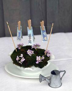 Geldwäsche Das brauchen Sie:  – weiße Sauciere  – Steckschaum  – Moos + ein paar kleinblütige Blumen  – zwei Schaschlik-Spieße  – dünner Draht  – kleine Holzwäscheklammern  – Geldscheine   So geht's:  1. Die Sauciere mit Steckschaum füllen. Das Moos draufsetzen und kleine Blüten einstecken.  2. Die beiden Schaschlik-Spieße links und rechts in den Steckschaum stecken und dazwischen aus dünnem Draht eine Leine spannen.  3. Mit den Wäs...