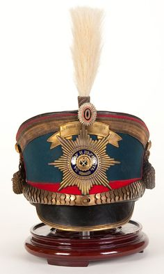 AN IMPERIAL RUSSIAN MOSCOVSKI GUARD REGIMENT OFFICER'S SHAKO OR KIVER. Model 1907 'Bell crown' shako with black leather top, royal blue wool rise and red band, piping, and black leather visor, with brass and enamel Guard Star plate, battle honor bandeau, chin scales and visor trim, as well as a cockade and horsehair plume. Complete with gold bullion crown braid, cords and tassels. Lined in black fabric and leather sweatband. - Jackson's International Auctioneers and Appraisers